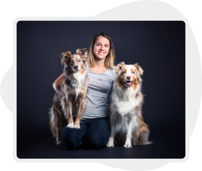 Picture of a woman sitting next to her two dogs and holding one in her hands